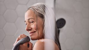 Woman smiling with enjoyment as she stands washing her hair with the raindance shower from hansgrohe #AllMyFeels